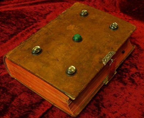 Vorderer Buchdeckel mit vier weißen und einem grünen Schmuckstein