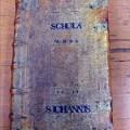 Buch mit Inschrift Schola S. Johannis auf dem Cover