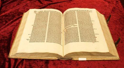 """Aufgeschlagene """"Sermones Sancti Augustini de tempore"""" mit zweispaltigem Text und Marginalien"""